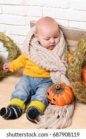 small baby boy with adorable curious face in yellow sweater leaned on pillow in knitted scarf around halloween decorations on white brick wall background