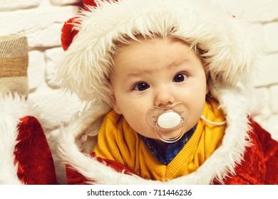 small baby boy with adorable curious face in yellow sweater laying on tummy with dummy in new year hat on white brick wall background