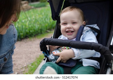 Small baby boy in the carriage in the park with his mother