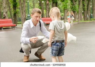 Small baby boy is eating cotton candy in the park with his father