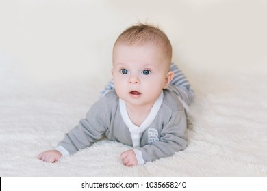 Small baby boy lying on stomach and raising his head awhile looking surprised and smiling cute, newborn