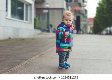 small baby boy standing and learning to walk. kid started to walk. 1 year old child doing first attempts to go.