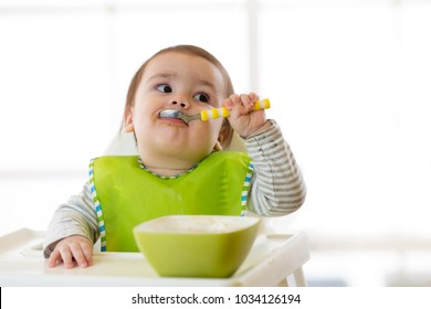 small baby eating healthy food with the left hand at home