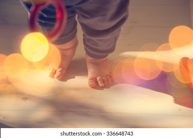 Small Baby Feet on Wooden Floor. First Steps Concept. Shallow Depth of Field. Toned Photo with Bokeh and Copy Space.