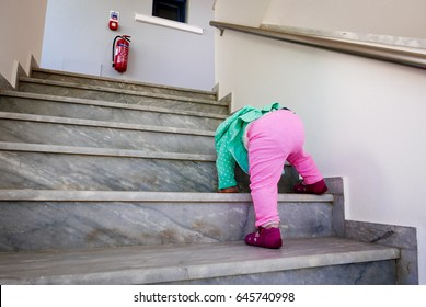 Small baby girl climbing at high stairs.