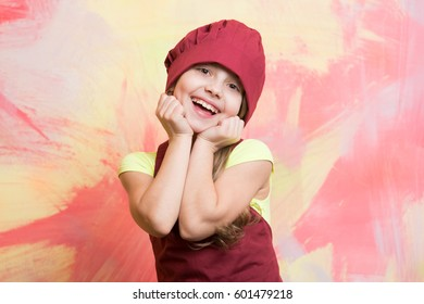 small baby girl or cute child with happy face in red chef hat and cook apron on colorful abstract background