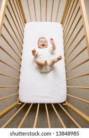 A small baby girl lying in a crib