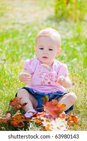 Small baby girl spending time outdoor on a warm autumn day.