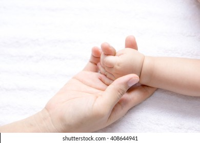 A small baby hand holding a finger