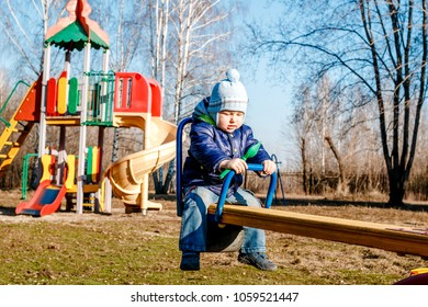 a small baby in a hat and a rut swings on a rocker in a spring Park on a Sunny day
