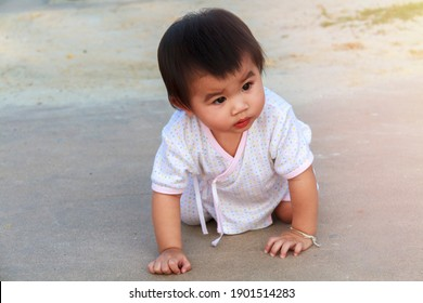 Small baby, little girl creeping, playing on road and sant at beach. Cute baby try to creeping and play on outdoor park. Little girl happy to creeping play at park.