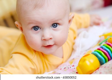 Small baby on the bed with the rattle bag watching you and smiling dressed in the orange night suit