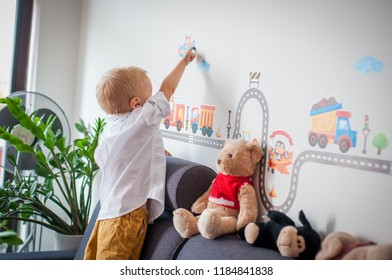 Small baby pointing with his finger on the wall. Young cute guy pointing on the wall and show toys.