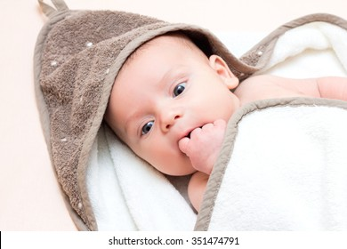 Small baby puts a finger in her mouth. Close up.