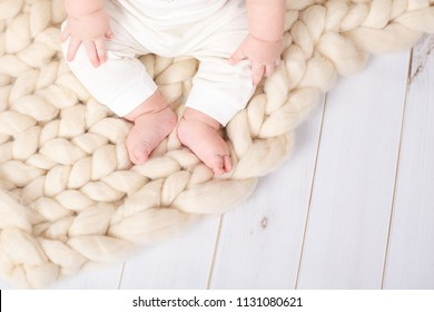 A small baby sitting on a blanket of Merino wool. Plaid on boards.