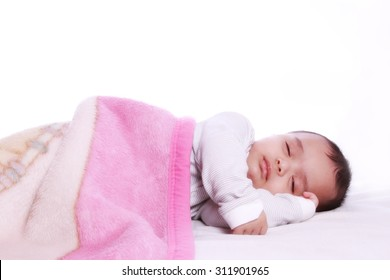 Small baby sleeping under a colorful blanket , photographed against white background.