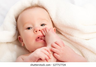 small baby sucking her finger on the leg