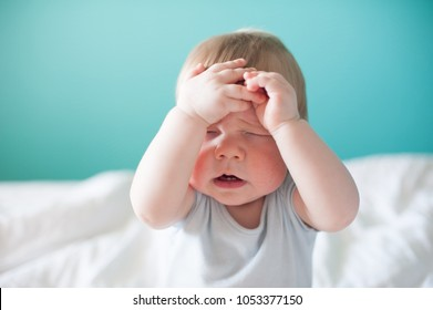 A small baby touched his hands to a discouraged face with closed eyes