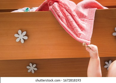 Small baby's hand pull out warm pink jacket from open wooden dresser. Mother's everyday life with young children at home. Maternity concept. Mess in stuff because of kids
