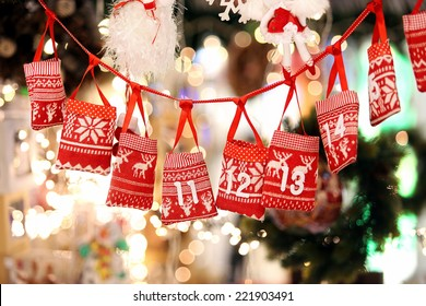 Small bags as Advent calendar with Sweets surprises hanging on a ribbon against lights blurred background