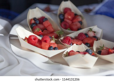 Small bamboo boats on a white plate holding seasonal berries and watermelon served as an appetizer at a party.