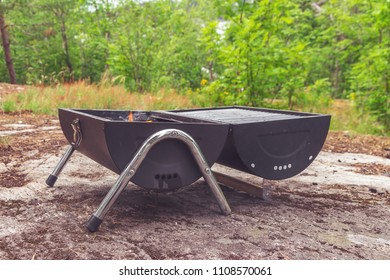 Small barbecue grill standing on stone hill among green trees. Outdoor fun and cooking meat, vegetables and marshmallow. Recreation photo collection. Flames coming from the coals of a small garden BBQ