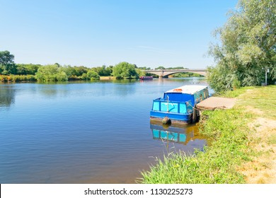 A small barge is tied up on the banks of the River Trent. In the distance another barge passes under a bridge.
