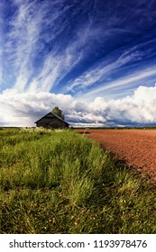 A small barn house on the edge of the field at the rural Finland. The summer clouds are forming dramatic formations on the sky in the background.