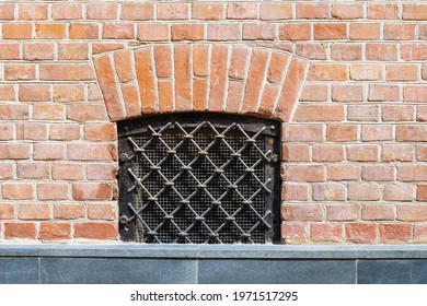 A small basement window in the brick wall. An old grate made of thick metal bars. Painted with black paint. Granite parapet.