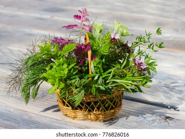 A small basket with healing herbs or kitchen herbs on wooden background.