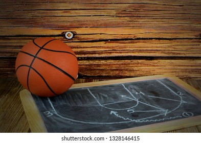 A small basketball and a chalkboard showing a classic pick and roll play, all on a wooden background with vintage filter applied