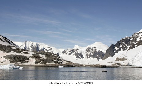 Small bay in Antrarctic peninsula. People on the shore and rubber boat is passing by