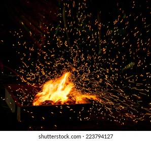 Small BBQ on fire with burning charcoal and flying sparks