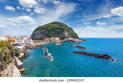 Small beach, cafes and hotels, giant green rock near small village Sant'Angelo on Ischia island, Italy. Sunny day, blue sky with white clouds and azure sea.