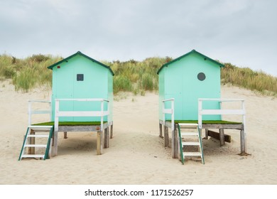 small beach houses with steps and a gate with in the background dunes with dune grass under a cloudy sky