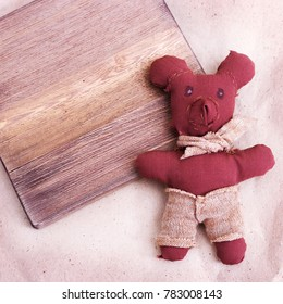 A small bear sewn by hand by a child. Soft toy bear with a scarf. A gift for a friend or mother. Copy space.