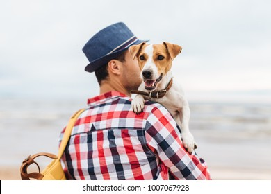 Small beautiful dog on owner`s hands. Stylish young male model dressed in fashionable clothes carries his pet and bag, stand at seashore, come to admire wonderful landscapes and breath fresh air