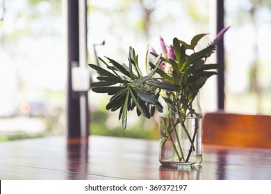 small beautiful flower in vase on table in room