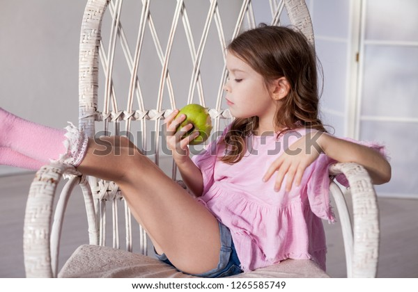 small beautiful girl eating fresh fruit Green Apple