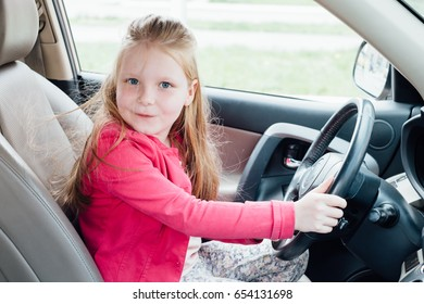 Small beautiful girl is steering wheel in the car