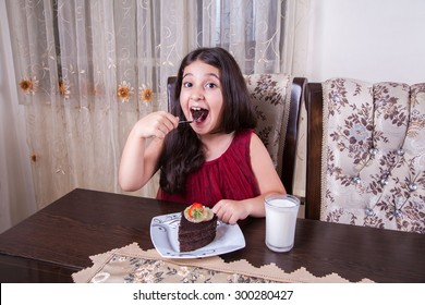 Small beautiful middle eastern girl with chocolate cake with pineapple, strawberry, milk, red dress, dark eyes, long hair, drinking, eating at home, sitting, smiling. looking at camera. studio shot.