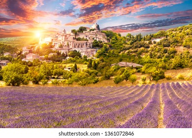 Small but beautiful old town of Simiane la Rotonde with a lavender field in front of it, Provence - France. Sunset time