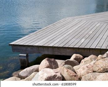 Small beautiful seaside wooden jetty dock pier deck by the ocean