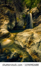 Small and beautiful waterfall forming a deep water hole surrounded by cliffs on Samothrace Island in Greece in a beautiful landscape scenery with a rock in the foreground