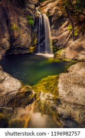 Small and beautiful waterfall forming a deep water hole surrounded by cliffs on Samothrace Island in Greece in a beautiful landscape scenery