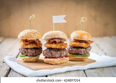 Small beef sliders grilled burgers onion rings little buns bacon served as appetisers for sharing