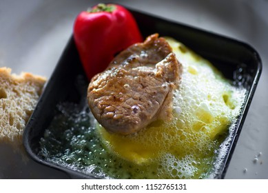 Small beef steak on hot cheese and red pepper on raclette pan grill, closeup.