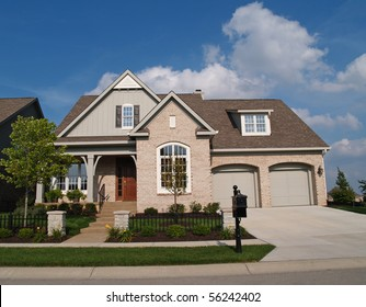 Small beige brick home with a two car garage in the front.