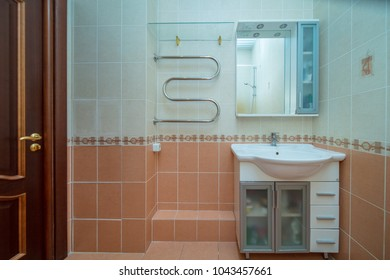 Small beige tile bathroom with bath tube and sink