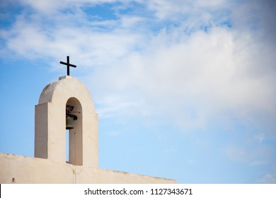 Small bell tower with a bell and a cross, and in the background a blue sky with clouds